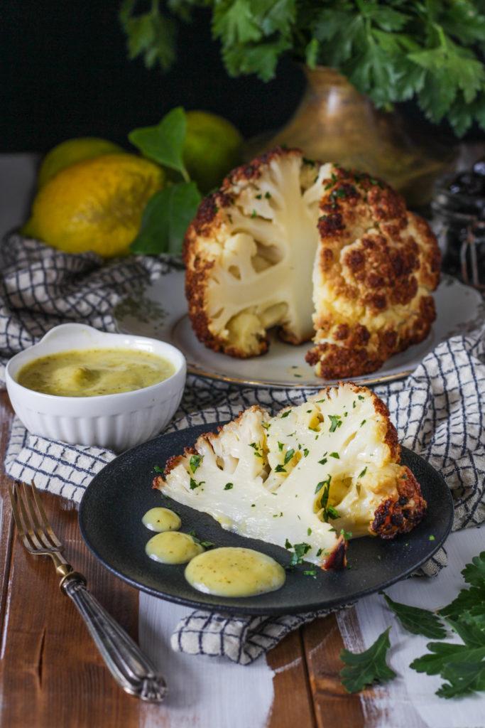 Fiore di cavolfiore al forno con salsa al limone ricetta vegan fetta pronta da gustare